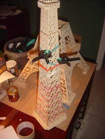 third section of the Eiffel Tower scroll saw wooden model held with elastic bands as it dries