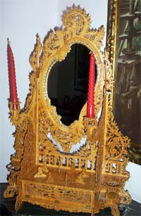 Italian dresser mirror made in fretworked wood with red candles on each side