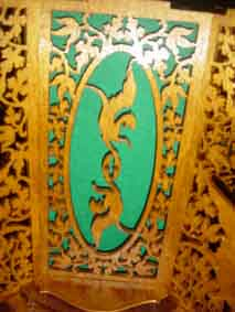 fretworked piece of the sun clock with the figure of a dragon and green felt