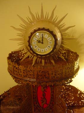 upper part of the sun clock, wooden golden sun with rays and a clock insert